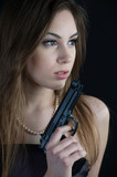Dangerous and beautiful woman with a gun