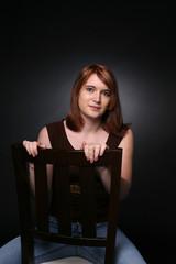 pretty teenage girl sitting backwards in a chair