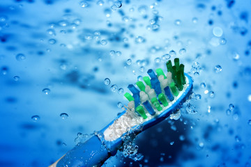 water splashing over toothbrush