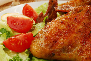 Grilled chicken wings with baked potatoes and vegetable salad