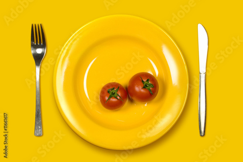 Ripe Tomatoes in yellow plate on yellow background