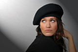 Woman with beret looking toward shaft of light. poster