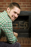Young man poking at fireplace poster