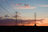 Sunset and a transmission tower on a field poster