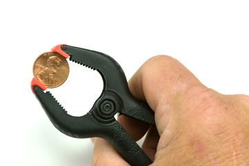 Hand gripping penny with clamp