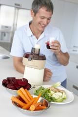 Middle Aged Man Making Fresh Vegetable Juice