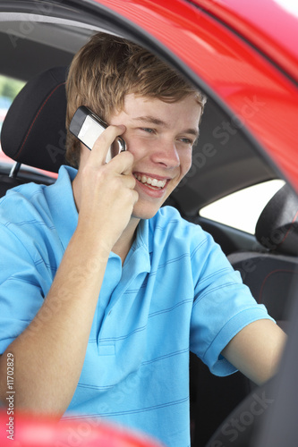 Teenage Boy Sitting In Car, Talking On Cellphone