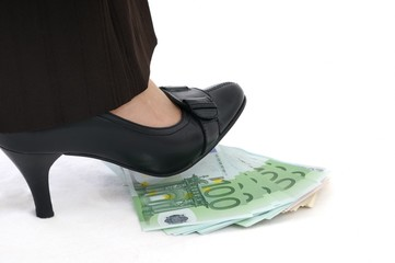 Woman leg steps on money