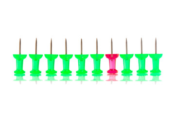 a red push pin stands in a row of green ones.