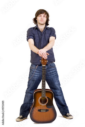 man holding his acoustic guitar between legs
