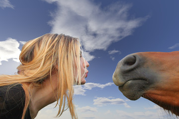 Girl face to face with a horse on blue sky.