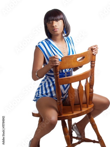 Young black woman straddling wooden chair blue top