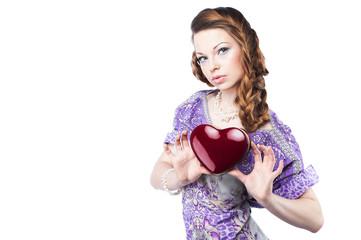 Beautiful romantic woman holding a dark red heart