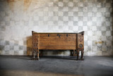 an antique wooden chest of drawers in castle at a stone wall poster