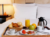 Fototapety Tray with breakfast on a bed in a hotel room.