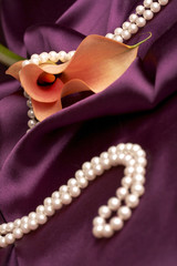orange calla and pearls on purple satin