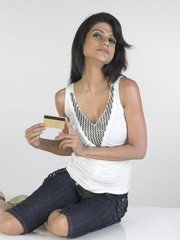 Modern girl in three-fourth pants  holding credit card