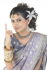 Woman in designed sari showing one finger