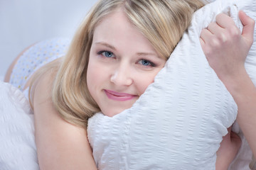 Smiling young woman resting in the bed