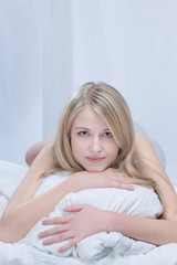 Portrait of blond woman on bed in bedroom