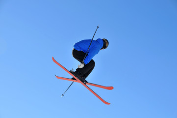 skier jumping with crossed skis