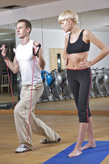 Young woman stretching with trainer