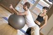 girl with a fitball and trainer in the gym