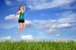rothaarige lachende Frau beim Springen über einer Wiese