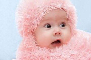 A surprised child in the winter scarf and a cap