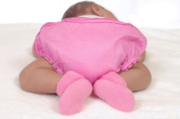 rear view of baby girl in pink bloomers, 3 weeks old