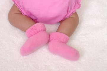 newborn baby girl's legs, three weeks old
