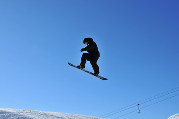 snoboarder in black on a high jump