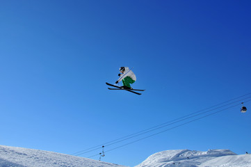 skier in green and white on a very high jump