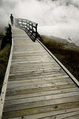 Person on a boardwalk disappears into mist from a body of water