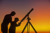 A father demonstrates to his child how to use a telescope - Fine Art prints