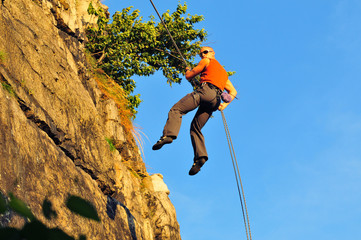 abseiling rock climber