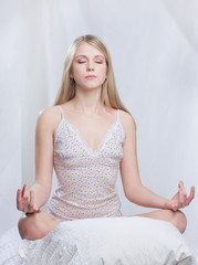 Young woman in lotus pose at morning meditation on her bed