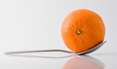 Metal tea-spoon with tangerine in it