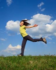 Girl jumping, running outdoor against blue sky