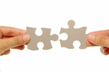 Hands joining two jigsaw pieces together poster