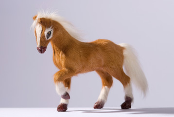 Friendly horse toy prancing on white