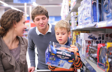 Parents with son with toy in shop