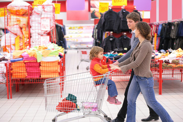 Parents roll cart with child in supermarket