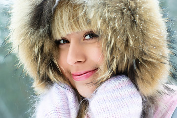 beautiful girl having a walk in the winter park
