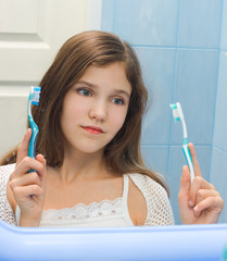Teen girl to decide between the two toothbrushes