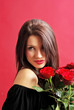 Young woman holding  rose on red background