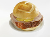 slice of leberkäse (type of meatloaf) in bread roll with heart