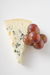 piece of blue cheese and red grapes