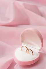 Wedding rings on background of the pink silk.