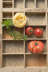 ribbon pasta, tomatoes and fresh herbs in type case